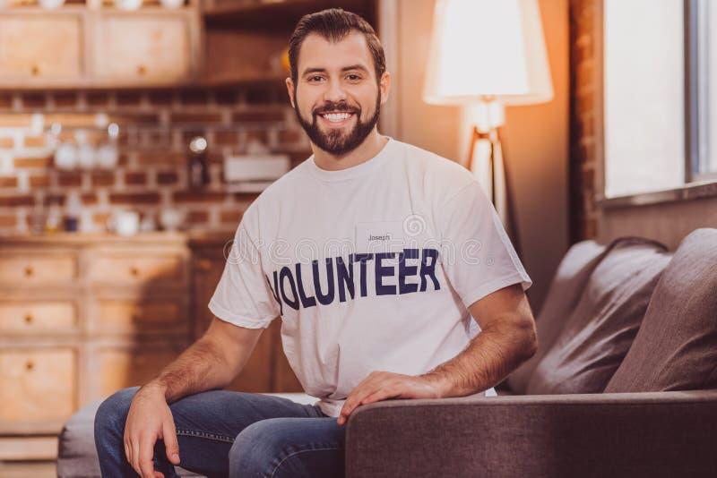 Glücklicher Freiwilliger, der auf dem Sofa strahlt und sitzt lizenzfreies stockfoto