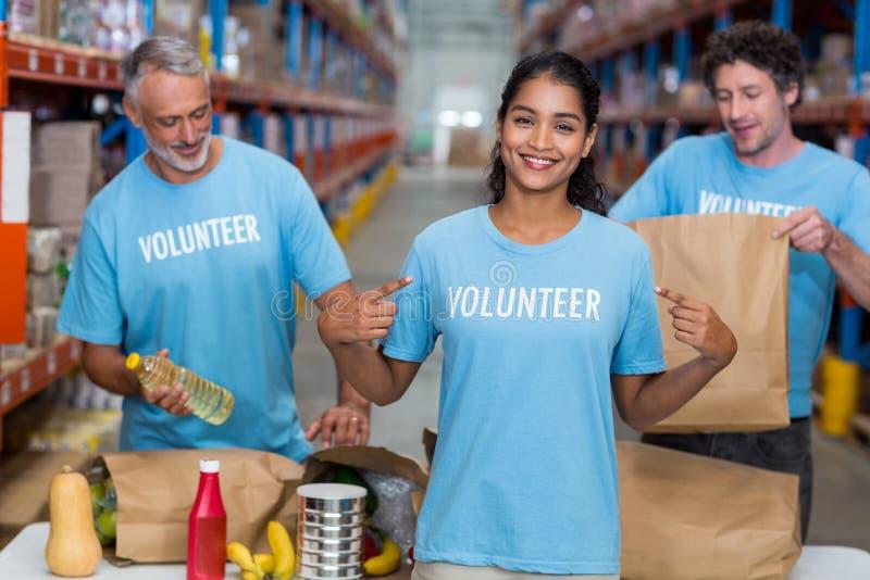 Glücklicher Freiwilliger, der ihr T-Shirt zur Kamera vor ihrem Team zeigt lizenzfreie stockbilder