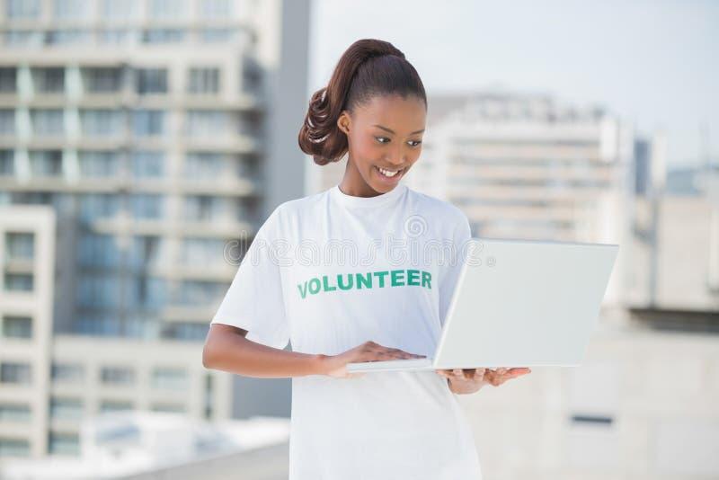 Glücklicher Freiwilliger, der Laptop verwendet lizenzfreies stockbild