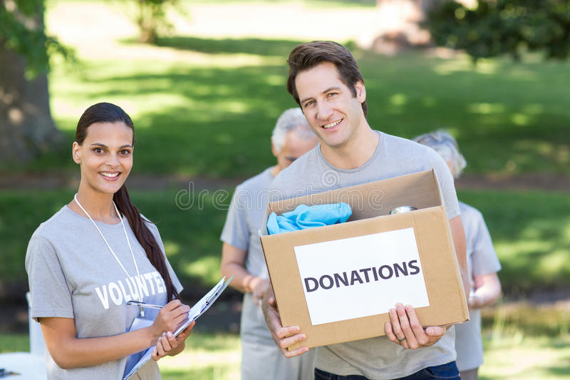 Glücklicher freiwilliger Mann, der Spendenkasten hält lizenzfreies stockbild