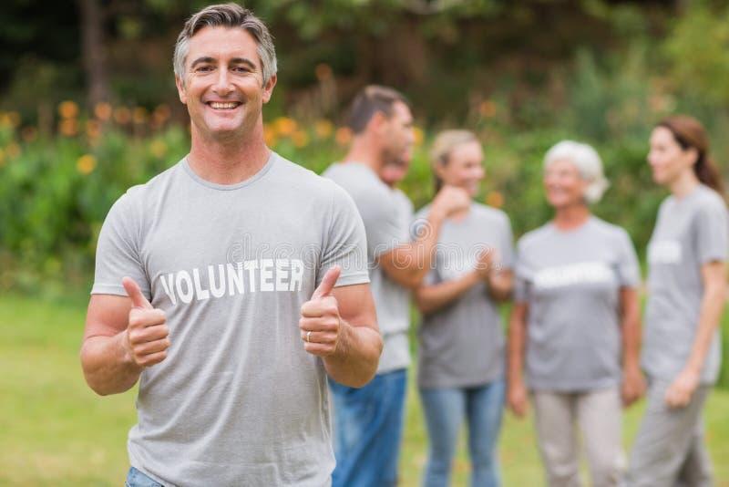 Glücklicher Freiwilliger mit dem Daumen oben stockfotos
