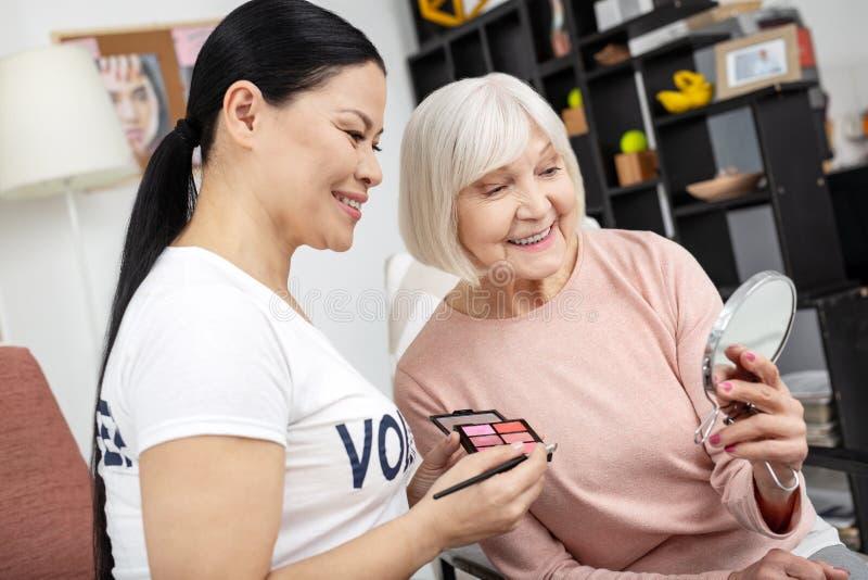 Glücklicher Freiwilliger und reife Frau bewundern maquillage stockbild