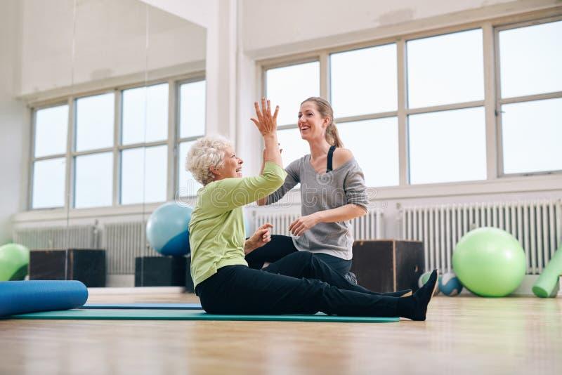 Glücklicher freuender Gesundheitserfolg der älteren Frau mit ihrem Trainer lizenzfreies stockfoto