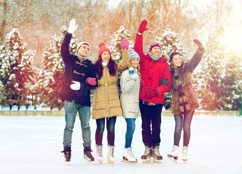 Glücklicher Freundeislauf auf Eisbahn draußen lizenzfreies stockfoto