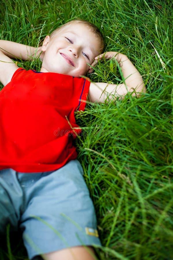 Glücklicher froher Junge, der auf frischem Gras sich entspannt lizenzfreies stockfoto