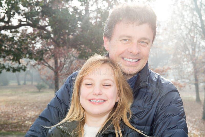 Glücklicher froher junger Vater mit seiner netten Tochter, die zusammen im Herbstpark genießend spielt, Zeit verbringend lizenzfreie stockfotografie