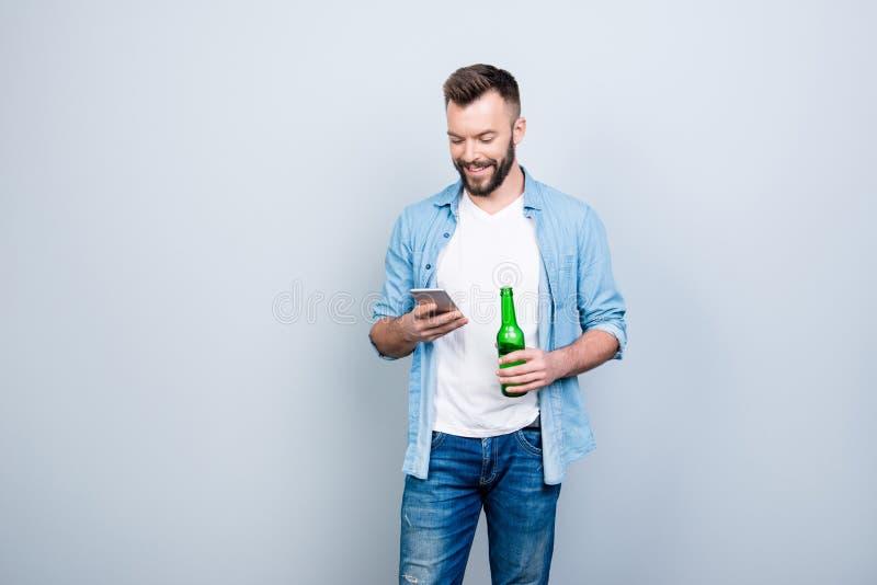 Glücklicher froher netter Junggeselle trinkt Bier und benutzt smartp stockfoto
