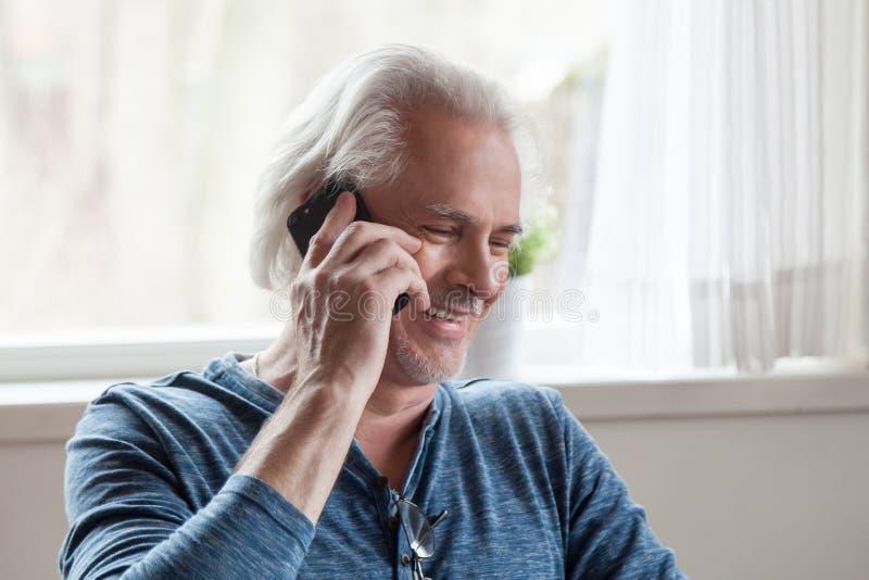 Glücklicher gealterter Mann, der lustiges Gespräch am Telefon hat stockfoto