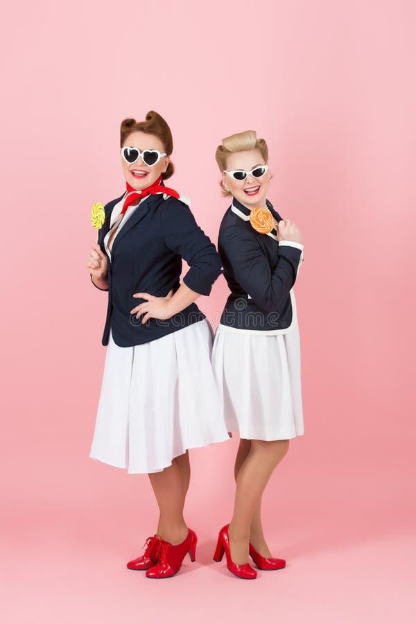 Glücklicher gelächelter Pinup redete Mädchen an die glückliche Stewardess laden ein, um zu lüften lizenzfreie stockfotografie