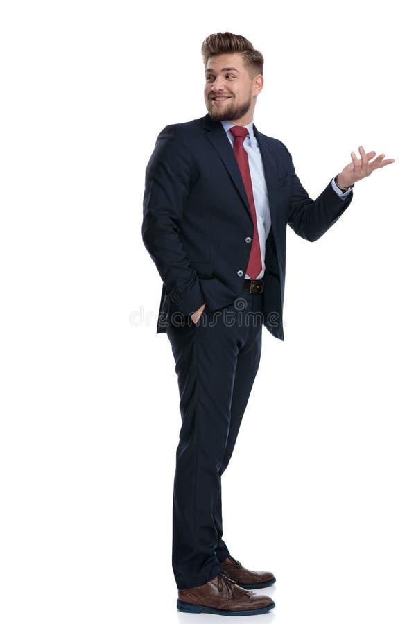 Glücklicher Geschäftsmann, der über seiner Schulter und Lächeln schaut lizenzfreie stockfotografie