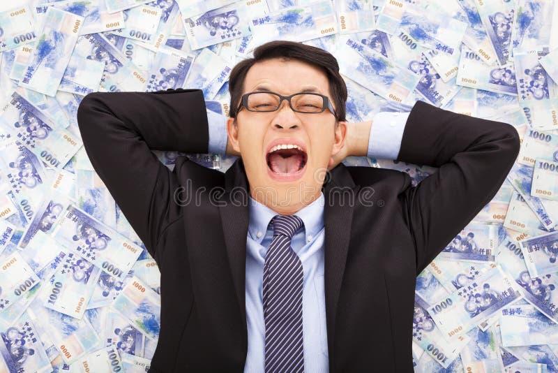 Glücklicher Geschäftsmann, der auf den Stapeln des neuen Taiwan-Dollars liegt lizenzfreie stockbilder