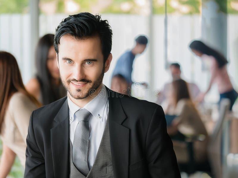 Glücklicher Geschäftsmann, der die Kamera, Büroangestellten, unternehmerische Entscheidungen betrachtet lizenzfreies stockfoto