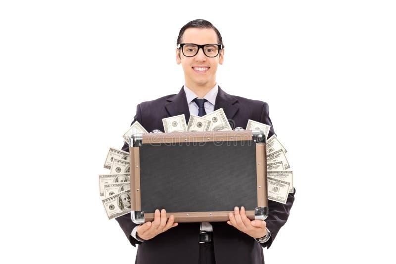 Glücklicher Geschäftsmann, der eine Tasche voll vom Bargeld hält lizenzfreie stockfotografie