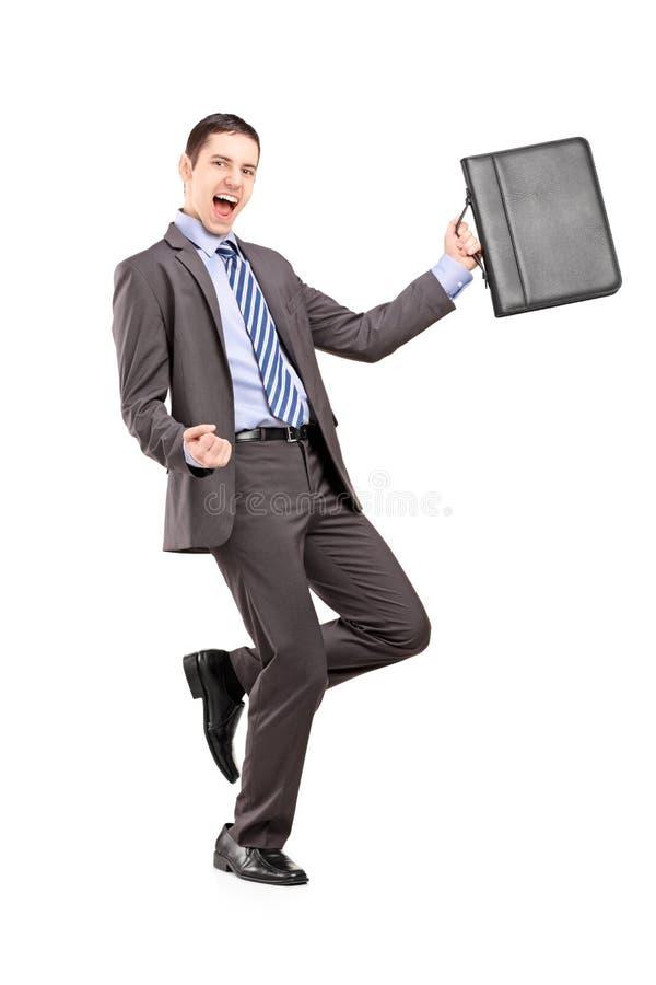 Glücklicher Geschäftsmann, der einen Aktenkoffer hält und Glück gestikuliert lizenzfreies stockfoto