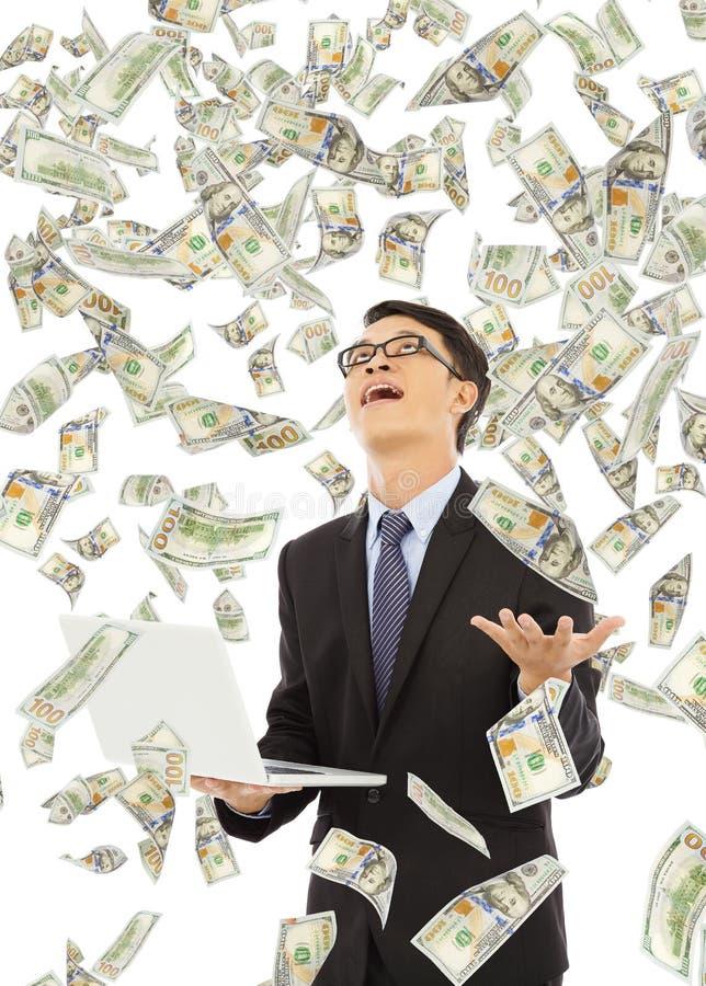 Glücklicher Geschäftsmann, der einen Laptop mit Geldregen hält stockfotografie