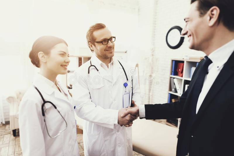 Glücklicher Geschäftsmann, der Hände mit Doktor rüttelt, der Unbehagen kurierte quittungen stockfoto