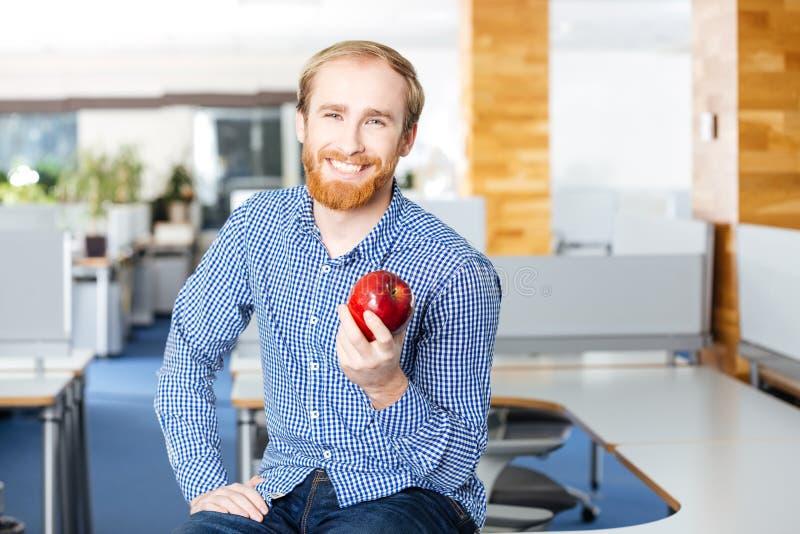 Glücklicher Geschäftsmann, der im Büro stationiert und roten Apfel hält lizenzfreie stockfotografie