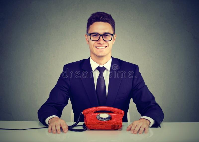 Glücklicher Geschäftsmann, der am Schreibtisch mit dem Weinlesetelefon betrachtet Kamera sitzt stockfotos