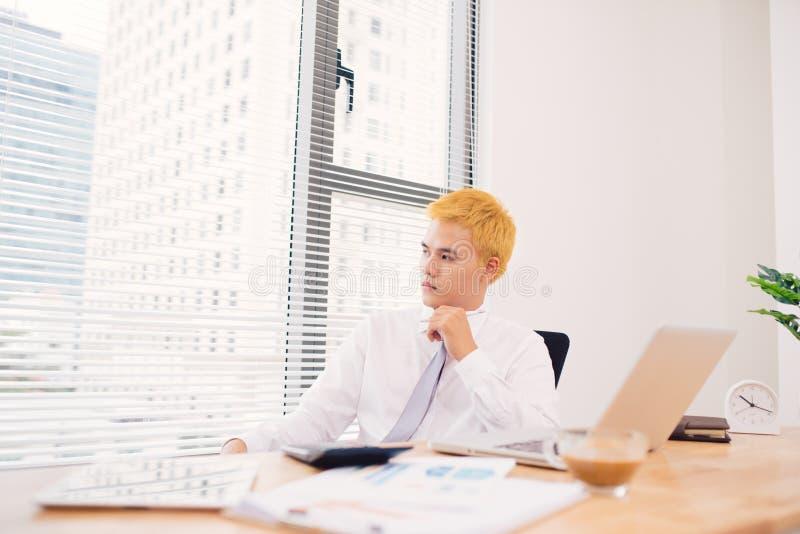 Glücklicher Geschäftsmann, der in seinem Büro mit Laptop arbeitet Junges smili stockfotos
