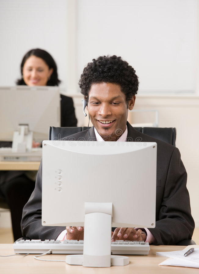 Glücklicher Geschäftsmann im Kopfhörer, der an Computer arbeitet lizenzfreie stockfotografie