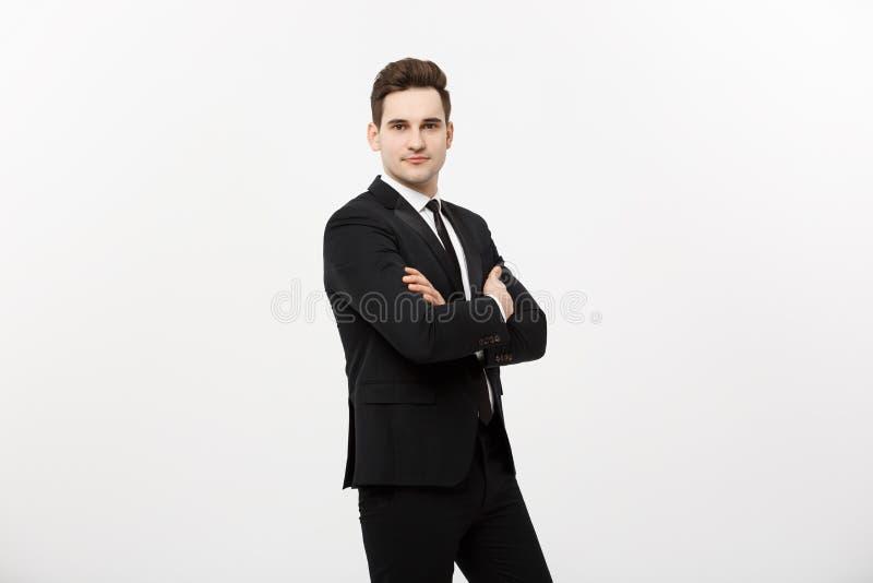 Glücklicher Geschäftsmann lokalisierte - den erfolgreichen gutaussehenden Mann, der mit den gekreuzten Armen steht, die über weiß stockbild