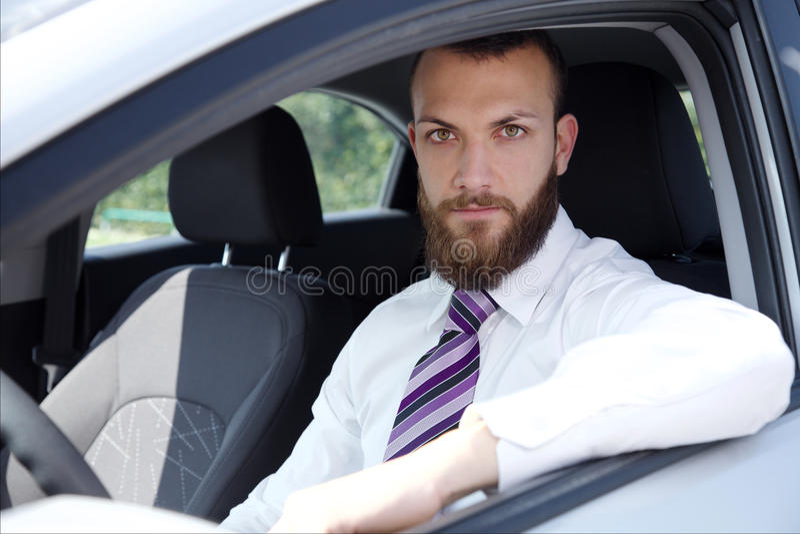 Glücklicher Geschäftsmann mit dem Neuwagen, der Kamera schaut stockfotos