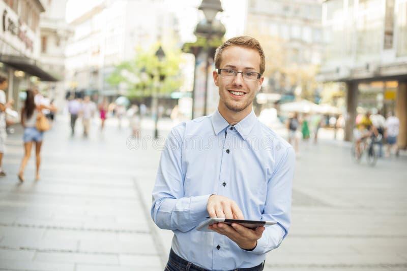 Glücklicher Geschäftsmann mit Tablette gehend auf Straße stockbild