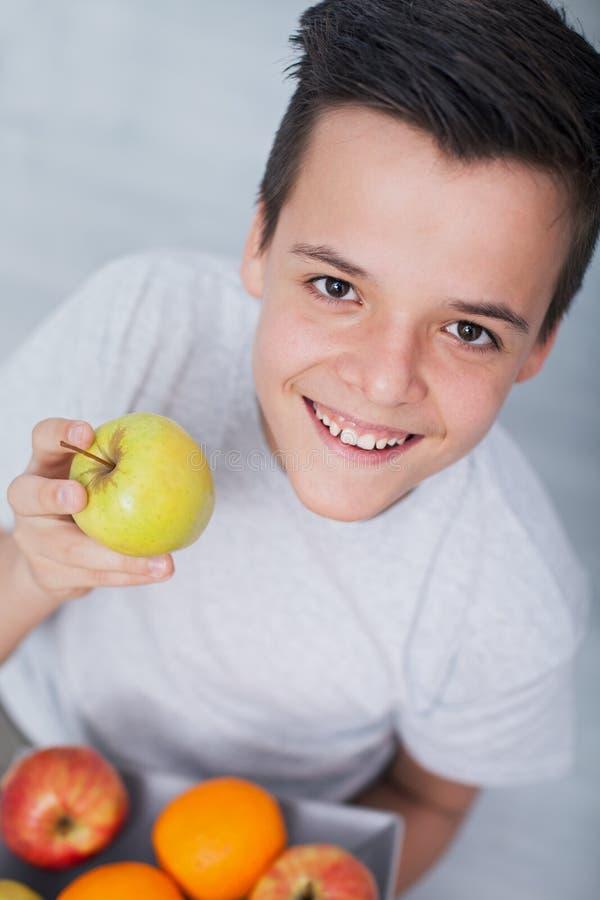Glücklicher gesunder Jugendlichjunge mit einer Platte von Früchten - einen Apfel halten, oben schauend lizenzfreie stockfotos