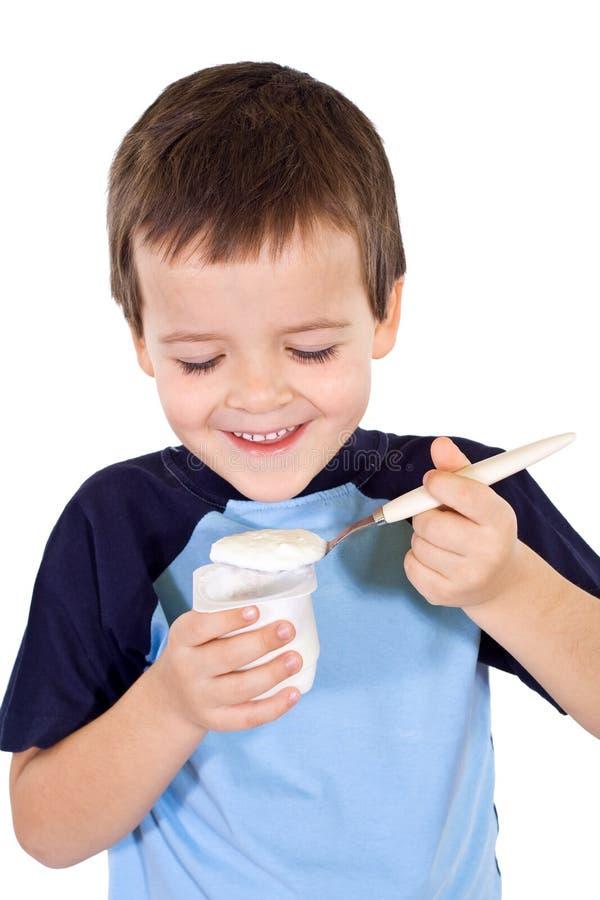 Glücklicher gesunder Junge, der Joghurt isst stockbilder