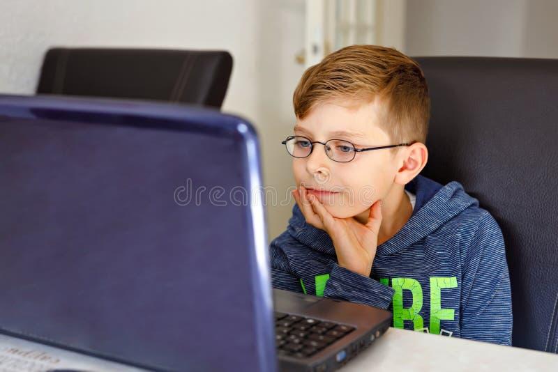 Glücklicher gesunder Kinderjunge mit den Gläsern, die zu Hause Schulhausarbeit mit Notizbuch machen Interessierter Kinderschreibe stockbilder