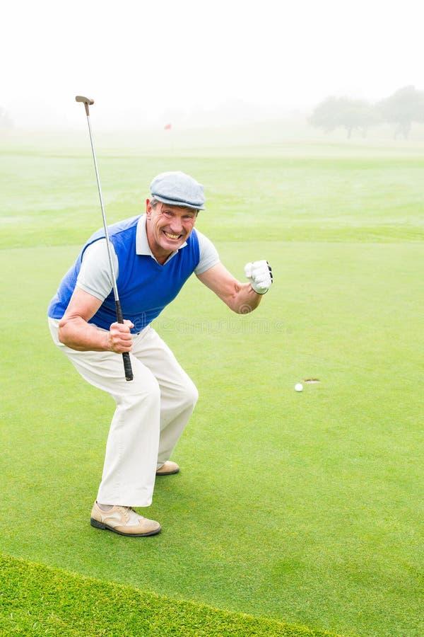 Glücklicher Golfspieler, der auf Übungsgrün zujubelt lizenzfreie stockfotos