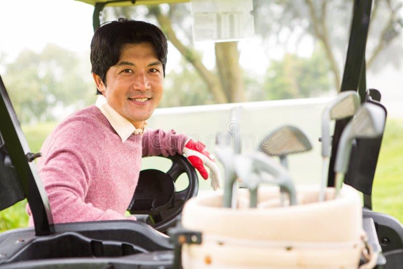 Glücklicher Golfspieler, der seins verwanztes Lächeln des Golfs an der Kamera fährt stockbilder