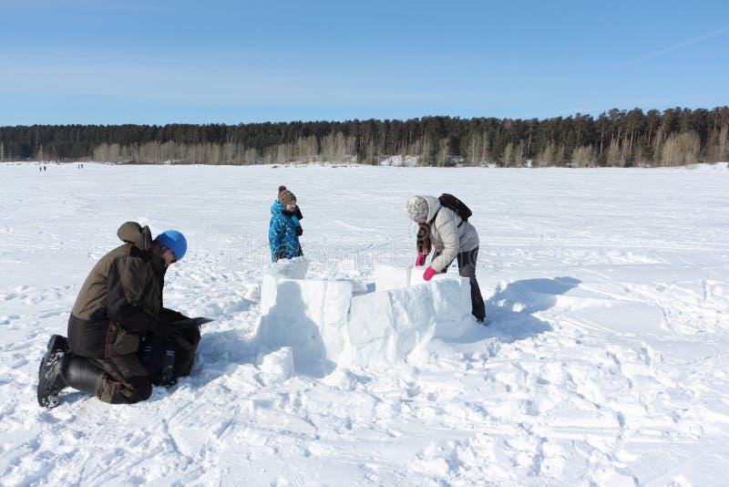 Glücklicher Großvater, Großmutter und Enkel, die einen Iglu auf einer schneebedeckten Lichtung errichtet stockbilder
