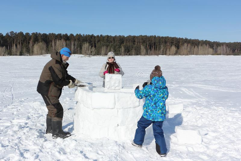 Glücklicher Großvater, Großmutter und Enkel, die einen Iglu auf einer schneebedeckten Lichtung im Winter errichtet lizenzfreies stockbild