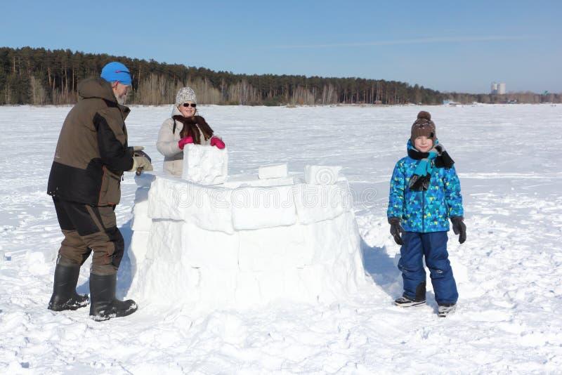 Glücklicher Großvater, Großmutter und Enkel, die einen Iglu auf einer schneebedeckten Lichtung im Winter errichtet lizenzfreie stockfotos