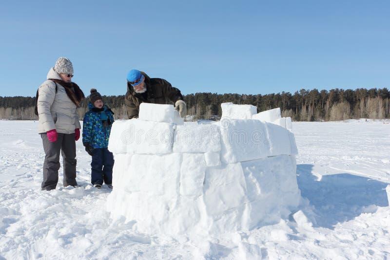 Glücklicher Großvater, Großmutter und Enkel, die einen Iglu auf einer schneebedeckten Lichtung im Winter errichtet stockbild