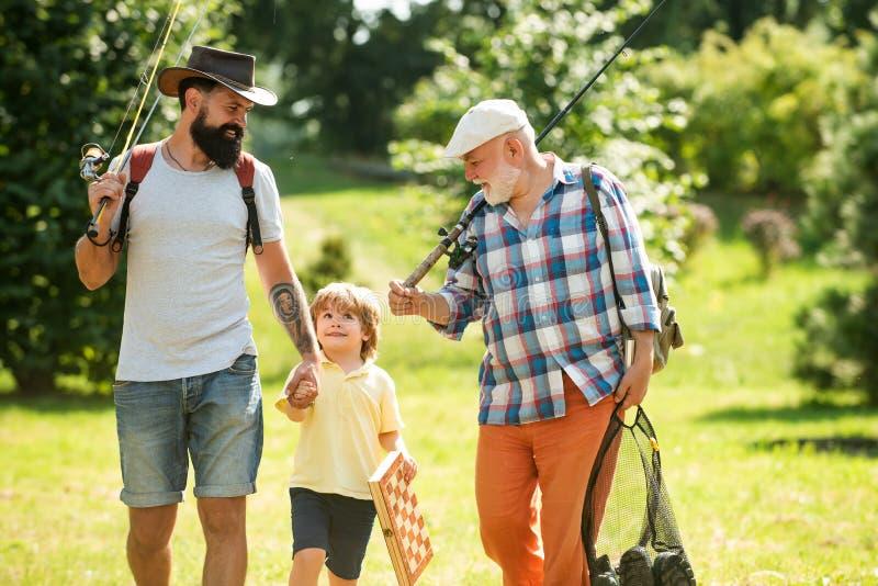 Glücklicher Großvater, Vater und Enkel mit Angeln anglers Manntag Großvater, Vater und Sohn fischen stockbild