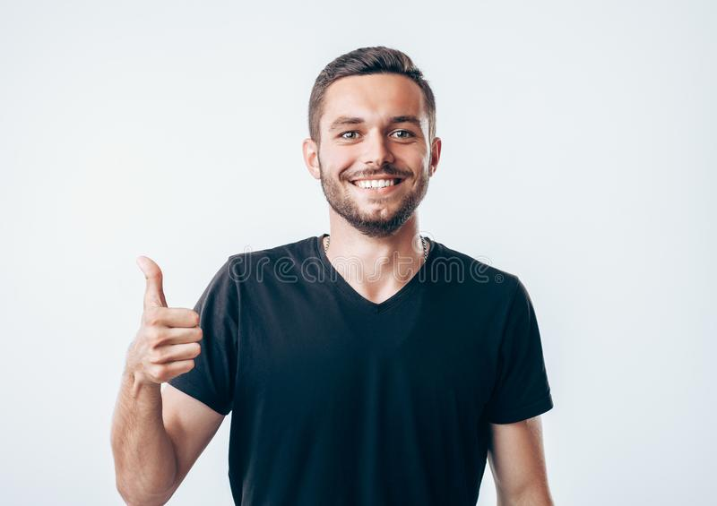 Glücklicher gutaussehender Mann mit Daumen sich zeigen stockbilder
