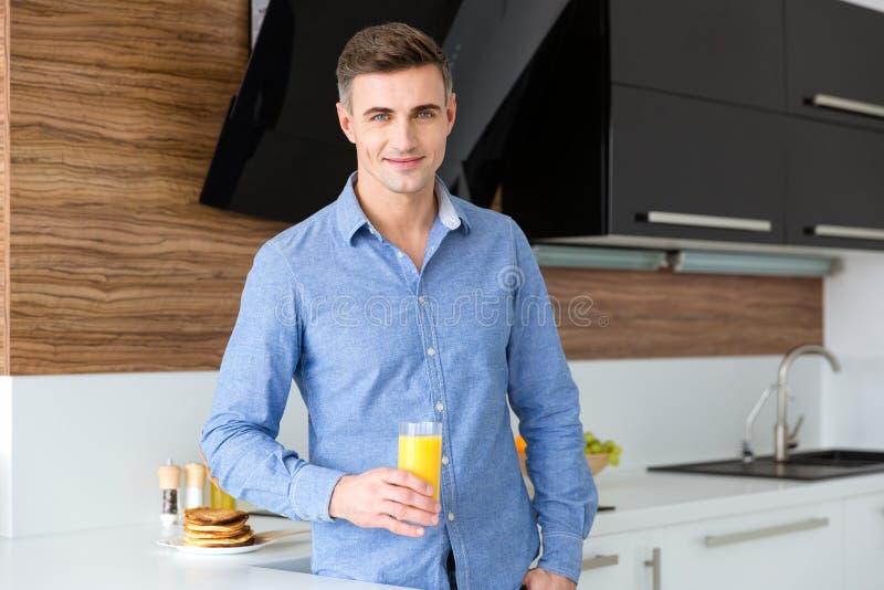 Glücklicher gutaussehender Mann mit Glas frischem Orangensaft lizenzfreie stockfotografie