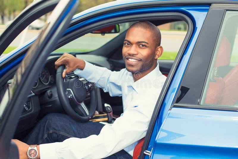 Glücklicher gutaussehender Mann in seinem neuen blauen Auto stockfotografie