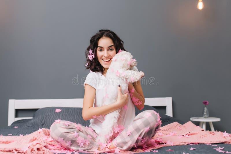 Glücklicher guter Morgen, wahre positive Gefühle der jungen frohen Frau in den Pyjamas mit dem brunette gelockten Haar, das Spaß  lizenzfreie stockbilder