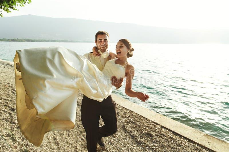 Glücklicher hübscher Bräutigam, der Braut in seinen Armen auf Strand am sunse hält lizenzfreies stockbild