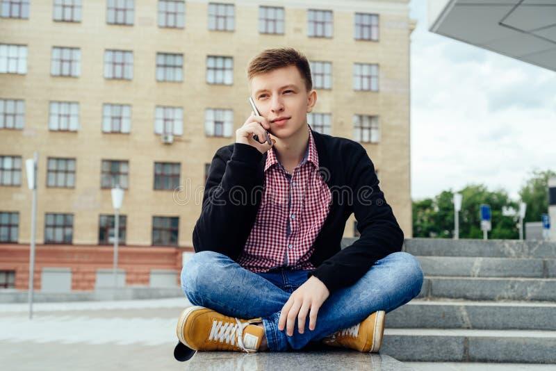 Glücklicher hübscher junger Mann, der auf Stein nahe Treppe sitzt und draußen am intelligenten Telefon in der Stadt spricht stockbild