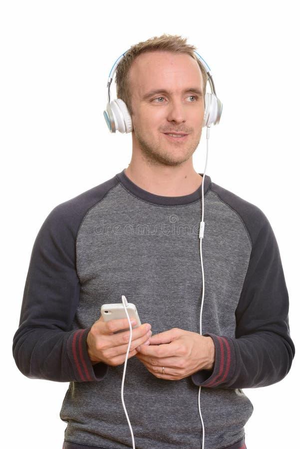 Glücklicher hübscher kaukasischer Mann, der Musik hört und mobi hält stockbild
