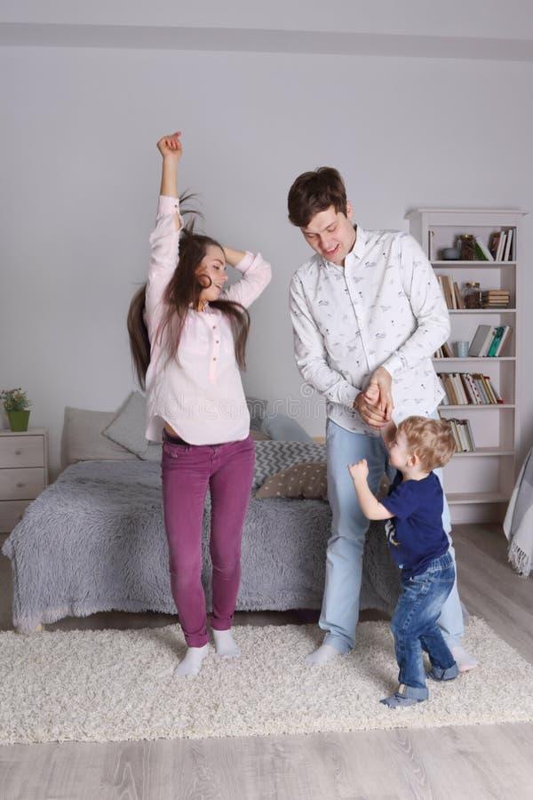 Glücklicher hübscher Vater, Mutter und kleiner Sohn tanzen stockbild