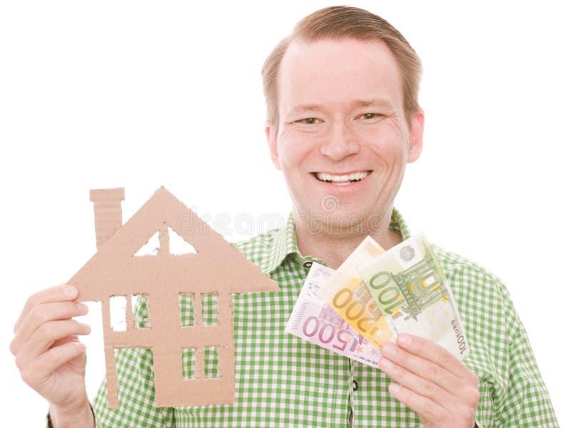 Glücklicher Hauseigentümer mit Geld stockfotografie