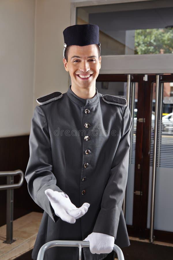 Glücklicher Hausmeister in der Hoteluniform stockbild