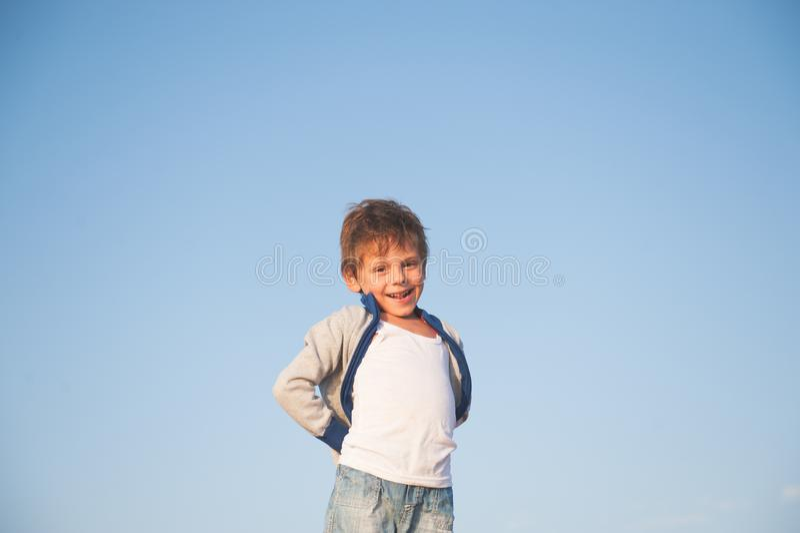 Glücklicher herrlicher lächelnder kleiner Junge in der Strickjacke auf Hintergrund des blauen Himmels stockfoto