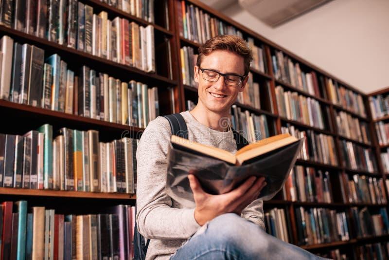 Glücklicher Hochschulstudent, der in der Bibliothek studiert stockfotos