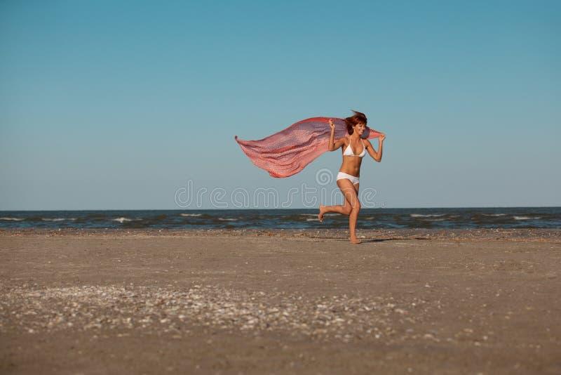 Glücklicher Holdingschal der jungen Frau auf Strand lizenzfreies stockbild